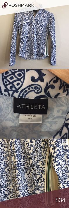ATHLETA Quarter Zip Top Very soft athletic top. White with blue pattern. White green and blue preppy stripes on sides. Crew neck. Silver quarter zip. Long sleeve. Soft interior. Good transition piece for fall or summer.  EUC Shoulder 15 Bust 16 Arm 23.5 Length 22 Athleta Tops Tees - Long Sleeve