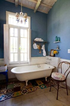 Claw foot tub, shuttered window and blue walls.