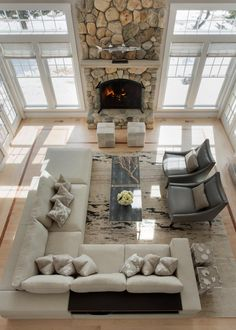 A dramatic floor to ceiling stone fireplace is the focal point in this two-story coastal style living room. A neutral sectional and wood coffee table add a touch of contrast to the bright look of the space, including soft beige walls and large windows that allow natural light to flood the room.                                                                                                                                                                                 More
