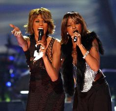 Whitney Houston and Erykah Badu smile at the 1999 Grammys.