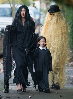Spooky: Myleene Klass, 37, showed off her scarier side as she went trick-or-treating with her two young daughters in north London on Saturday, dressed as Morticia Addams and her daughter as Wednesday
