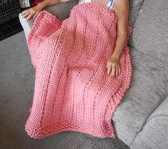 """Lovely super chunky throw/blanket that measures 41"""" X 46"""" in a Coral colour    Made from a yarn which is a blend of 20% wool and 80% acrylic. A Truly individual item.      As with all hand knitted items true measurements are difficult and each piece is individual so no 2 items will be exactly the same.          Wash at 30 degree on delicate cycle or hand wash. Dry flat, do not iron or tumble dry. Can be dry cleaned.          This item comes from a smoke and pet free home.   Shop this product…"""