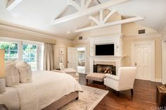 Traditional Master Bedroom with stone fireplace, Crown molding, Cathedral ceiling, Hardwood floors, Carpet