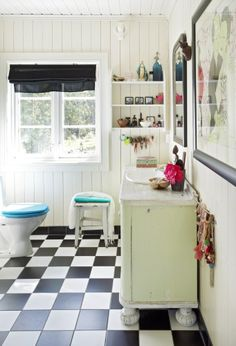 white bathroom - black and white floor - black curtain and picture frames