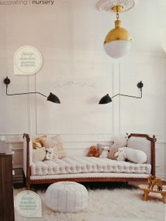 Chic kids room. Love the modern Serge Mouille fixtures above the antique bed. White leather pouf ottoman.
