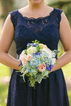 bridesmaid in navy lace dress with scoop neckline and holding traditional bouquet with roses, hydrangea, and greenery