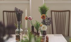 tapered candles and natural florals in recycled glass bottles #designsponge #dssummerparty