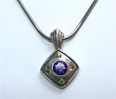 John Atencio Amethyst Pendant - Amethyst Pendant designed and signed by John Atencio. Made in sterling silver and 18kt yellow gold. A250-102. (subject to prior sale) -- Lilliane's Jewelry -- 4101 W. 83rd St. Prairie Village, KS 66208 -- 913-383-3376 –