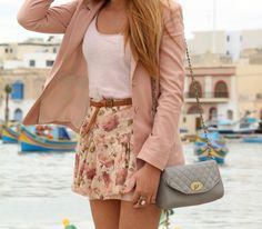 A pale pink blazer, simple white tank, floral skirt, braided belt, and patent purse.