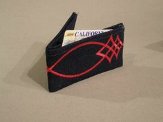 Denim business card/credit card holder with red embroidered stitching.