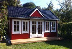 Clockhouse Gartenhaus, dessen Giebel aus dem blauschwarz gedeckten Dach farblich besonders hervor sticht. http://www.gartenhaus-gmbh.de/