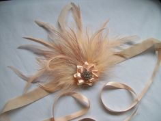 Peach & Cream Feather & Rhinestone Vintage Style Flapper Band, Downton Gatsby Order Now from www.indigodaisyweddings.co.uk Specialising in stunning bespoke cocktail fascinators and formal hats in a wide range of colours, perfect for Royal Ascot and The Kentucky Derby. Plus all your wedding floral accessories including shoe clips, vintage flapper bands, feather and flower fascinators, feather fans, fairy wands, wrist corsages, wedding bouquets & buttonholes. Worldwide Delivery.