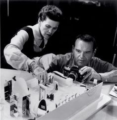 Charles & Ray Eames taking photos of a model