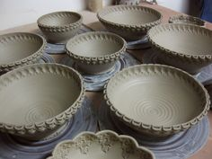 Using homemade stmps on ceramic bowls. Really like this man's work.