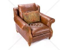 pillow on a chair - A plush brown leather couch with a decorative pillow on a white background