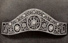 A diamond and natural pearl kokoshnic, 1910. Featuring three diamond motifs, each with a natural button pearl in the centre, supported by diamond foliates and flower heads, with greek key terminals; and topped by a band of laurel leaves interspersed with button pearls and circular diamonds, all held within band of diamonds top and bottom.