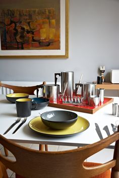 Arne Jacobsen serving set and cutlery, Wegner folding chairs.