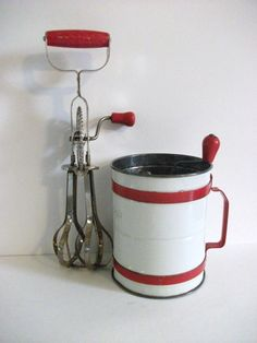 Vintage  red-handled egg beater and red and white flour sifter .