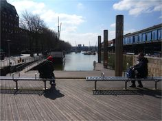 The timber decking in the public realm in Bristol Docks proved to be slippery when wet and after several months was altered to include some non-slip sections. Some seating is provided which enables people to experience a pleasant view over the water but thee benches do not have backrests. It is difficult to determine the edge of the docks from the photograph.  Image courtesy of Sandra Manley, UWE. Pleasant View, Slippery When Wet, Timber Deck, Public Realm, Decking, Benches, Bristol, Photograph, Water