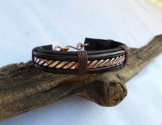 This leather and copper bracelet is entirely hand made. The way the hand cut and dyed leather compliment the hand forged copper gives this bracelet its rustic yet elegant appearance. The copper has been hand hammered and twisted then polished to a near mirror finish that can be