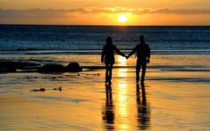 A couple walk hand in hand along Tynemouth beach, North Tyneside, as the sun rises after a week of bad weather  Picture: Owen Humphreys/PA