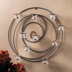 Lend an artistic touch and soft candlelit glow to your room with this unique and appealing wall sconce. Its circular metal coils hold 10 glass candle cups that await the tea light candles of your choice, and its entrancing beauty can't be ignored! Candle Wall Decor, Iron Wall Decor, Wall Candle Holders, Candle Wall Sconces, Wall Sconce Lighting, Candle Stands, Candle Cups, Glass Candle, Tea Light Candles