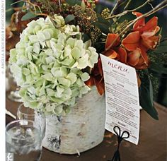 Regan and Michael's florist created a mix of tall and short birch-covered vases to hold branches, fall leaves, antique hydrangea, hypericum berries, seeded eucalyptus, and cymbidium orchids.