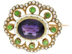 A suffragette brooch, c.1910–15, in gold, demantoid garnets, pearls and white enamel and amethyst; the green, white and vermillion colours refer to the slogan 'Give women votes'. (The Antique Jewellery Company)