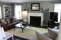living room with gray walls, brown leather couch, white fireplace, black curtain rods