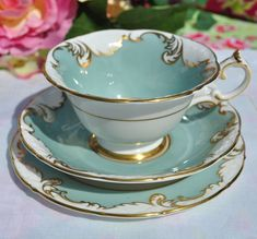 Paragon Richelieu rococo style vintage fine bone china teacup, saucer and tea plate trio. Duck egg blue - green with an embossed white acanthus leaf and swirls border outlined with elaborate hand painted gold gilding. Lavish gold gilding to the scallop shaped rims, tea cup foot and handle and double inner gold circles. A beautiful collectible tea cup trio with a lovely scroll handle. Teacup 10.5cm wide at the rim x 6cm tall. 14cm Saucer and 15cm Tea Plate. Paragon China made at the Atlas…