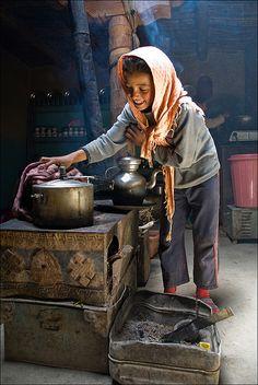 "A girl preparing the ""vegetables"" on the stove traditional Ladakhi. Village Pidmo - Zanskar"