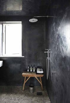 Dark bathroom. Floor is tiled with pebbles from Fired Earth.