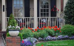 Gorgeous red tulips in front of this pretty porch. From Front-Porch-Ideas-and-More.com