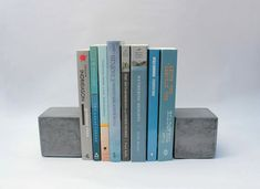 Simple and inexpensive. Adds raw element to shelving with precious white items. [Modern Concrete Bookends Cube by roughfusion on Etsy]