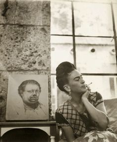 Photo of Frida Kahlo with self-portrait drawing by Diego Rivera (1930), Coyoacan, circa 1945. Photo by Manuel Alvarez Bravo.