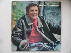 "John Davidson on a bike. Cover of his album. Ecstatic Wax says, ""This record goes to show that you can stuff a schlock-slinging goober into a leather jacket and put him on a motorcycle and he'll still be a schlock-slinging goober."""