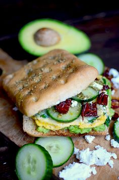 This recipe beats a McMuffin any day! A scrambled egg with spinach and cheese, avocado smash, cukes, sun dried tomatoes, and pesto on rosemary foccacia make the ultimate breakfast sandwich!