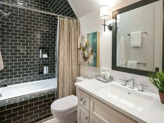 "The private bathroom continues the bedroom's color scheme with a contemporary twist. The floor-to-ceiling glass subway tile ""follows the roofline, so you're using as much space as possible,"" says interior designer Linda Woodrum.  http://hg.tv/vb3p"