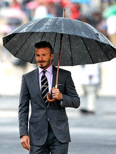 "Original Caption: ""Beckham and a brolly."" What the hell is a Brolly?  If it's a british term for umbrella I'm totally using it from now on because it's fun to say."