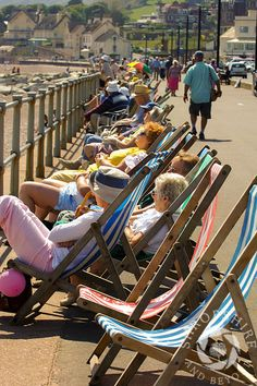 Oh I Do Like to Be Beside the Seaside! Sunbathers on the seafront at Sidmouth, Devon, England.