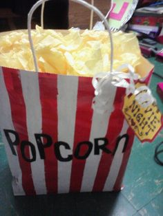 Paint a bag to look like a popcorn sack, and use yellow tissue paper to make it look like popcorn. put his favorite dvd and movie treats like candy & popcorn inside.