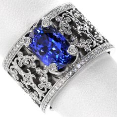 Intricate pierced scrolls created in 14k white gold and adorned with bead set diamonds. For Design 2352, the natural 3.50 carat cushion cut blue sapphire is embraced with four regal, diamond capped prongs. Hand applied milgrain finishes our Knox Signature heirloom band. #engagement #wedding #ring www.knoxjewelers.biz
