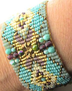 Gorgeous Chili Rose Metallic Amethyst & Turquoise Gemstone Bracelet Stunning hand woven loomed bracelet that features diamond shape patterns of spectacular color combimations-Purple-Cream-Turquoise (green & blue)-Olive Interlocking hidden closure adorned with faceted gemstone inlay-Amethyst , Peridot and Turquo