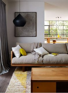 Tom Dixon light (?) I think. Taupe/grey couch and walls - yellow is brought in via accessories and a hint of it in the carpet. Natural wood plays well with this color scheme.