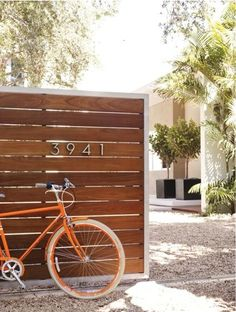 midcentury house numbers + black planters + wood half fence + white vase with pale peach/tan trim + orange door + sculptural greenery