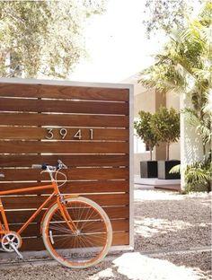 midcentury house numbers + black planters + wood half fence + white vase with pale peach/tan trim + orange door + sculptural greenery