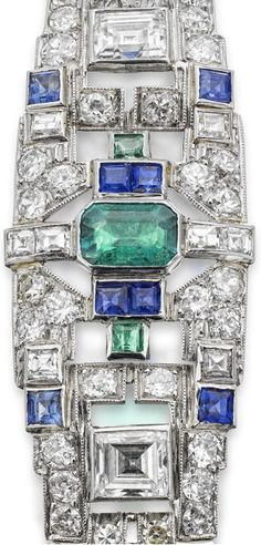 An Art Deco gem-set bracelet, circa 1930. The tapered frontispiece set with an octagonal-cut emerald between a pair of baguette-cut diamonds, in turn between a pair of oval-cut sapphires, all to a geometric framework set throughout with carré-cut sapphires and emeralds and with circular and carré-cut diamonds, the gallery engraved, the back an expandable strap.