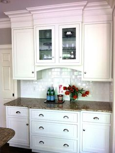 White cabinets with subway tile backsplash. Crown molding to ceiling.