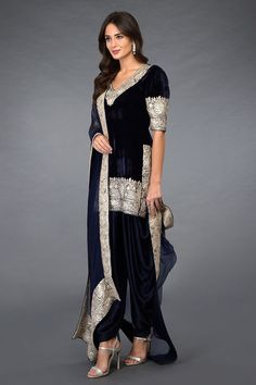 Midnight Blue Kashmiri Silver Tilla embroidered tunic kurta and dupatta paired with dhoti salwar pants. The midnight blue silk velvet kurta is adorned with Kashmiri silver tilla embroidery on front neckline, sleeves, side sl Pakistani Dresses Online, Indian Gowns Dresses, Indian Designer Outfits, Designer Dresses, Silk Kurti Designs, Velvet Dress Designs, Princesa Real, Velvet Suit, Dress Indian Style