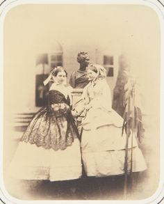 Photograph of Princess Victoria, Princess Royal (1840-1901), later Empress Friedrich of Prussia, standing in right side profile and facing the viewer. On the right stands Princess Alexandrine of Prussia (1842-1906), later Duchess William of Mecklenburg-Schwerin, who faces Princess Victoria. Behind them is a bust of an unidentified female on a plinth. A sapling stands on the right of the picture.